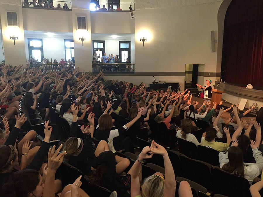Students raise their arms, following the instructions of speaker Sister Marianne Keena on April 15. photo by Zoe Butler