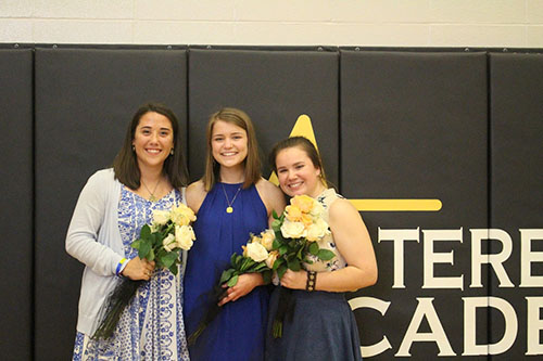 Senior and Academy Woman Hallie Ryan, center, poses with fellow nominees Kat Mediavilla, left, and Maddy Medina, right, at the Awards Ceremony today. The girls received the traditional rose bouquets presented to Academy Woman nominees at the annual Awards Ceremony. photo by Mary Hilliard