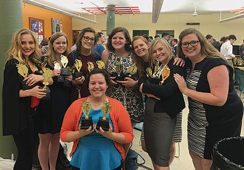 Six of the eight debaters present at Wednesday's championship round, with debate team moderators Kate Absher and Alicia Stewart, pose with STA's trophies from the night and the year as a whole. photo courtesy of Joseph Gose