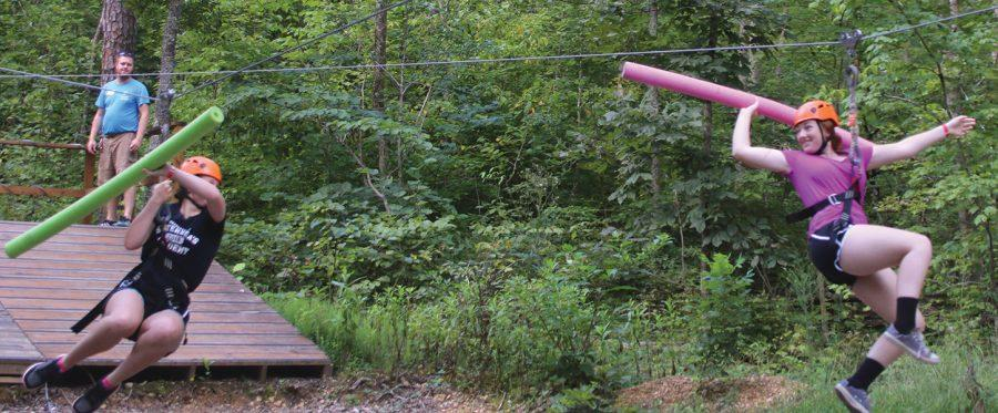 Juniors Amelia Schulte, left, and Kate Willnauer prepare to attack each other with pool noodles while ziplining at the STA Singers retreat Aug. 20. photo by Madi Winfield