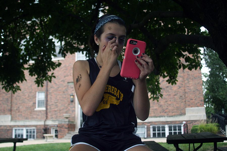 Senior Libby Terril applies fake blood during a practice for the spirit club's annual fall sports pep rally Aug. 31. photo by Cassie Hayes