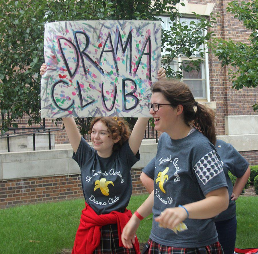 Sophomore Reilly Donnelly holds up a Drama Club sign while Junior Courtney Talken tries to get people to join the club. photo by Paige Powell