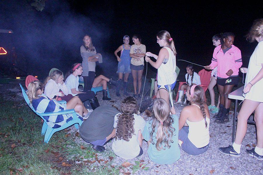 The tennis team gathers around the campfire while some roast marshmellows at the tennis team campout on September 16. photo courtesy of Hannah Zastrow