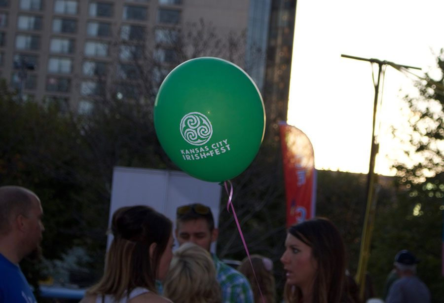 An Irish Fest balloon floats through the crowd tied to someone's hand. The Irish Fest balloons were free and came in green and white. photo by Anne Claire Tangen
