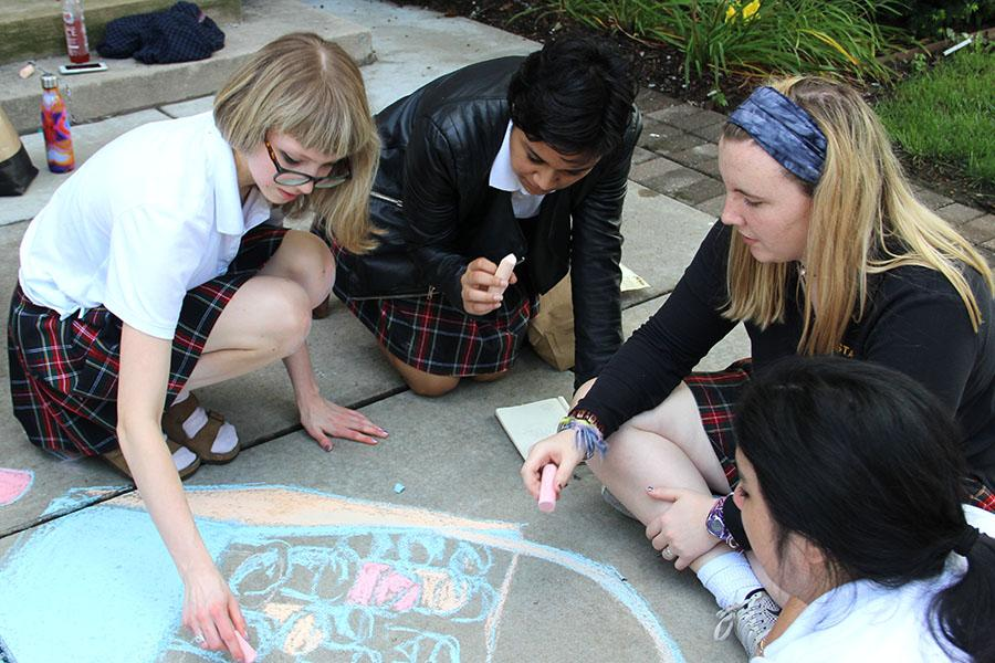 Senior Ellie Grever, from left, junior Yasmeen Mir and junior Annie Mullen contribute to their advisory's chalk drawing. Grever, Mir and Mullen are members of the Reynolds advisory. photo by Anna Louise Sih