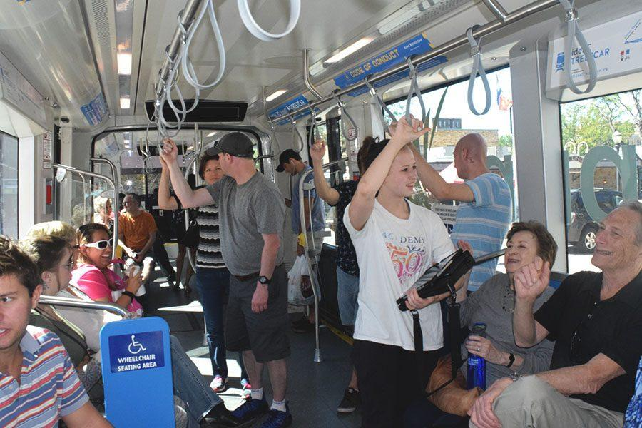 A couple from Pennsylvania, Corey and Rebecca (center left), stand and hold on as the streetcar approaches the first stop of the tour while Sophomore Anne Claire Tangen (center) talks with her grandparents, Rita Messina and Mike Messina.