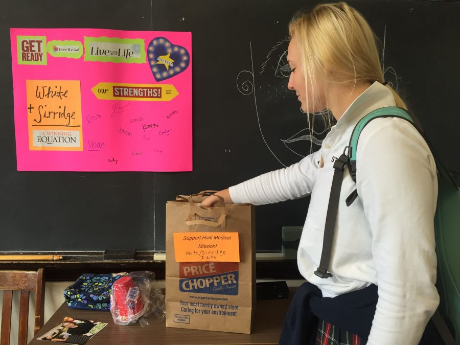Senior Ellie Brewer places the items she bought in her advisory's donation bag. French Club will be accepting donations until Friday. photo by Zoe Butler