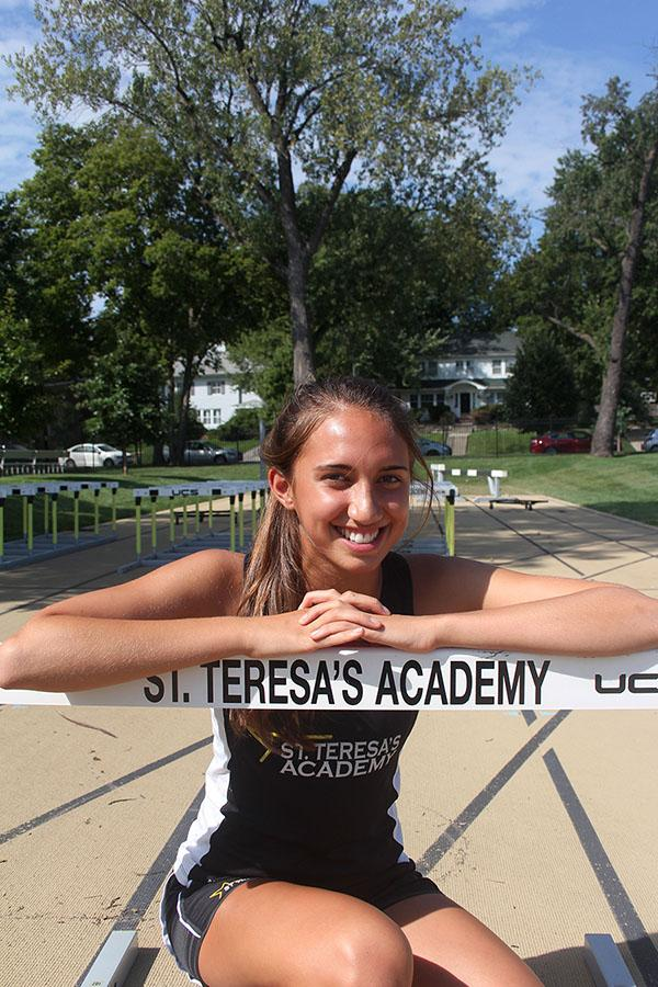 Junior Mia Schloegel poses for a photo by a track hurdle. Schloegel has been on varsity cross country since she was a freshman. photo by Gabby Ayala