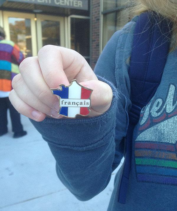 Junior Emma Boxx holds a french club pin in front of the Goppert Center. photo by Victoria Cahoon