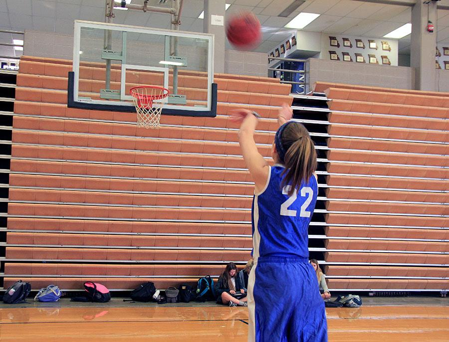 Junior Natalie Kistler shoots a freethrow to warm up for her team's first CYO basketball practice Nov. 30 in Goppert. The team practiced in preparation for their first game Saturday, Dec. 3.  photo by Sophie Sakoulas