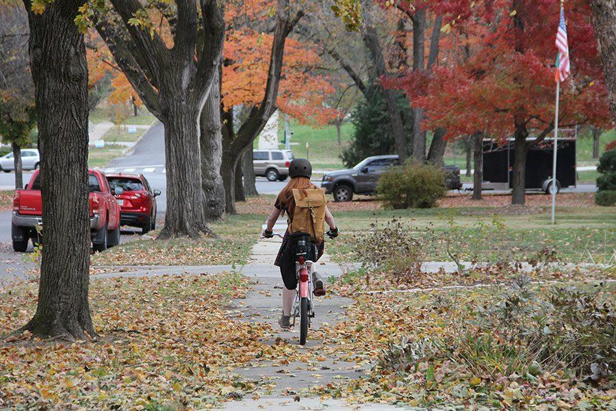 Junior Isabella Fitzpatrick rides her bike down the sidewalk of E 56th Street after school Nov. 22. photo by Alex Davis