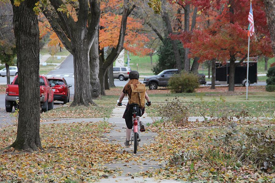 Junior Isabella Fitzpatrick rides her bike down the sidewalk of E 56th Street after school Nov. 22. photo by Alex Davis