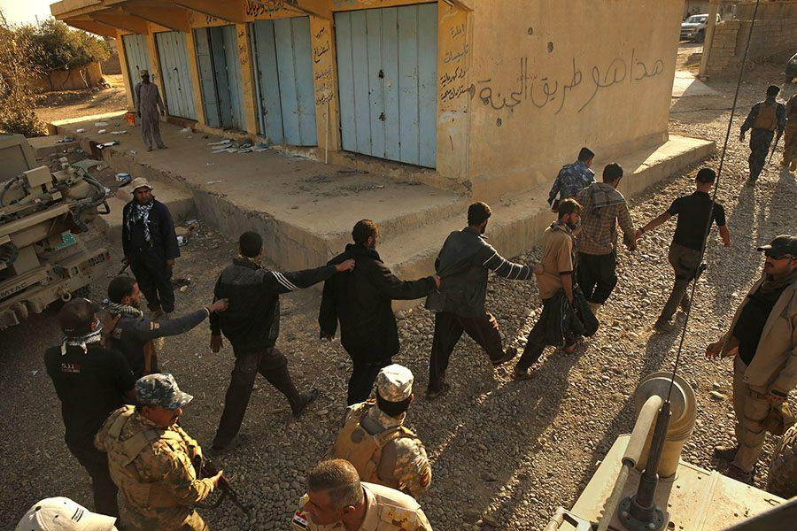 In the town of Salhyia, members of the Iraqi Army and Iraqi police detain and question suspects who were coming from the direction of Mosul, Nov. 4. photo courtesy of Tribune News Service