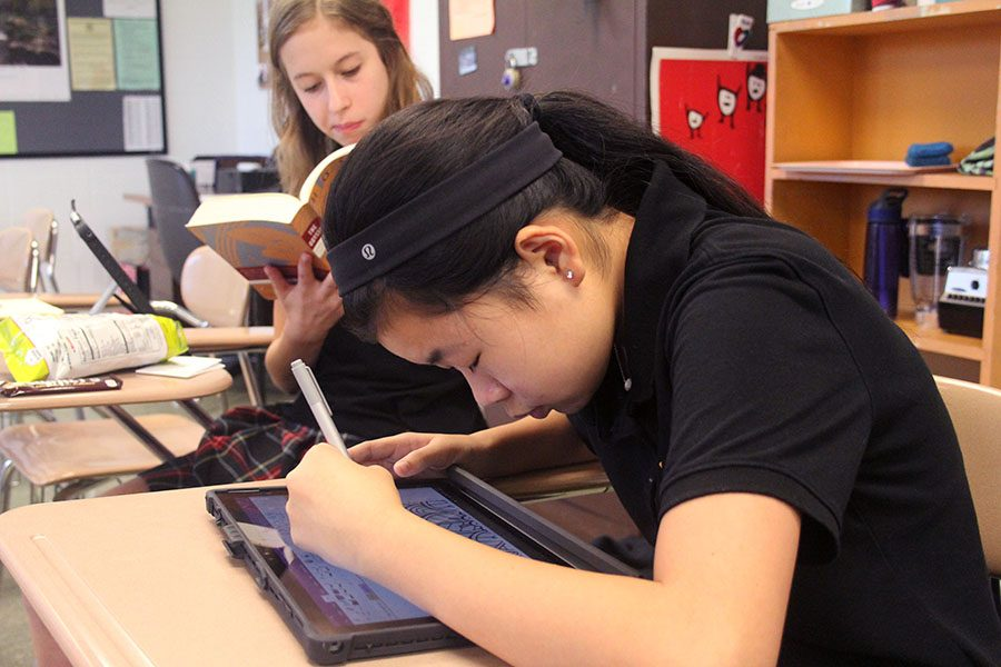 Freshman (left) Katherine Kallas reads a book while Emma Peck (right) draws on her Surface Pro. Both freshmen come to Whitney aftercare on most school days. photo by Gabby Ayala