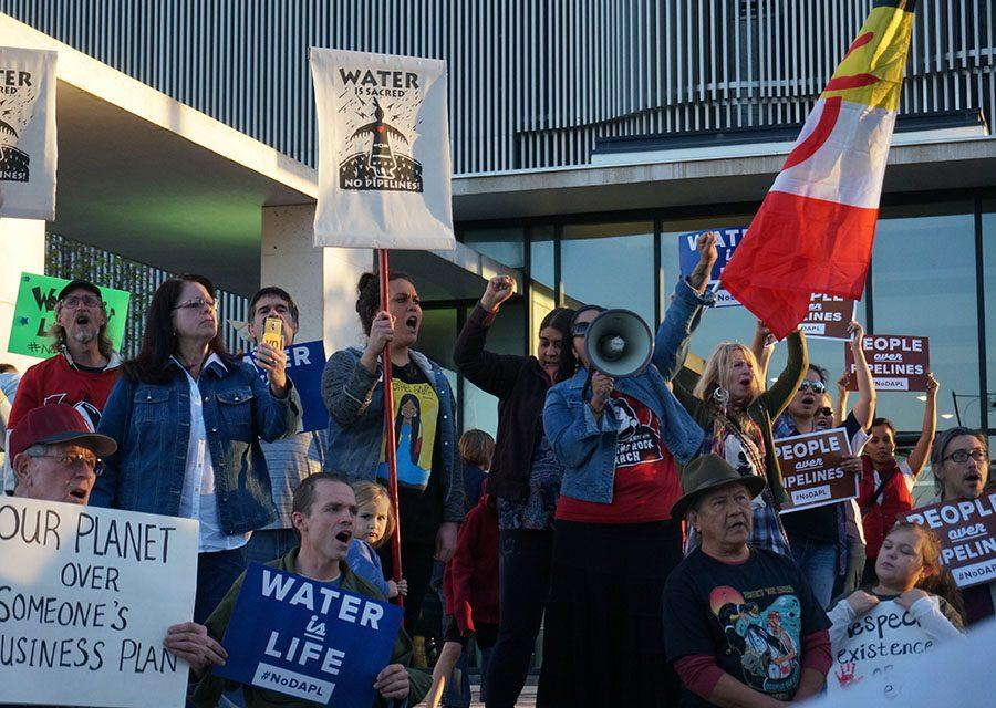 Protestors of the Dakota Access Pipeline chant in front of the Richard Bolling Federal Building Nov. 15. During the protest, people used a megaphone to chant, sing songs and pray. photo by Gabby Martinez