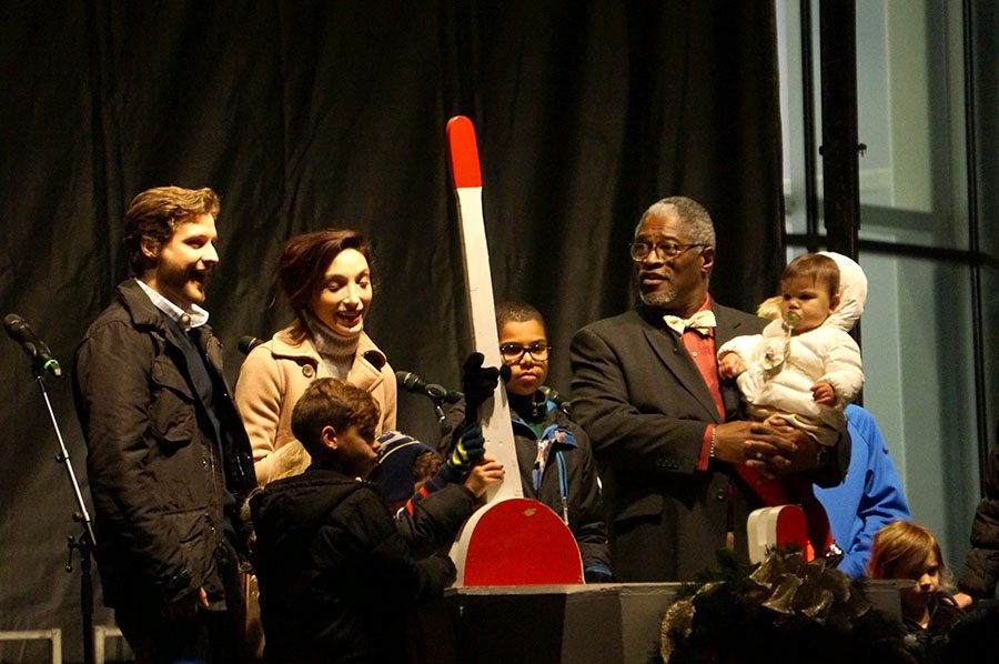 Kansas City Mayor Sly James joins his guests, which include Olympic skating champions Charlie White and Meryl Davis, on stage for the flipping of the switch. The 100-foot-tall tree was lit up Nov. 25 during the Mayor's Christmas Tree Lighting Ceremony. photo by Gabby Martinez