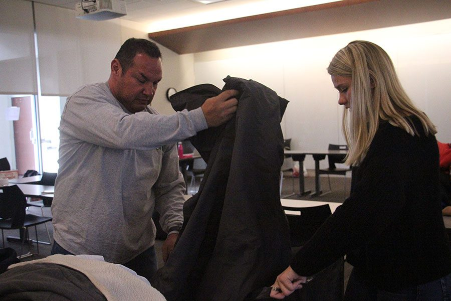 Mark Trujillo, left, puts coats into a bag as Social Justice Club Co-president Regan Reda holds the bag open at the STA Coat Drive Dec. 3. The Coat Drive broke a Guinness World Record from collecting 2,631 coats. photo by Sophie Sakoulas