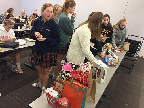 FBLA members crowd around a table which secret santa gifts. photo by Catherine Ebbits