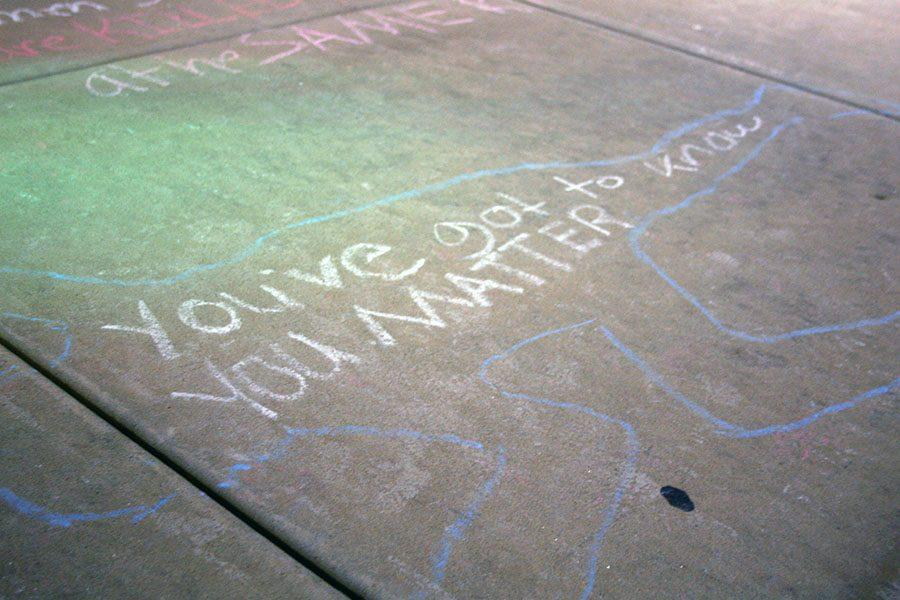 Chalk drawings are displayed in front of the Aquarium Dance Studio during the 'Every 28 Hours' performance Oct. 17. Local volunteers perform and recite stories based on the statistic that every 28 hours, an African American person is killed. photo by Cassie Hayes