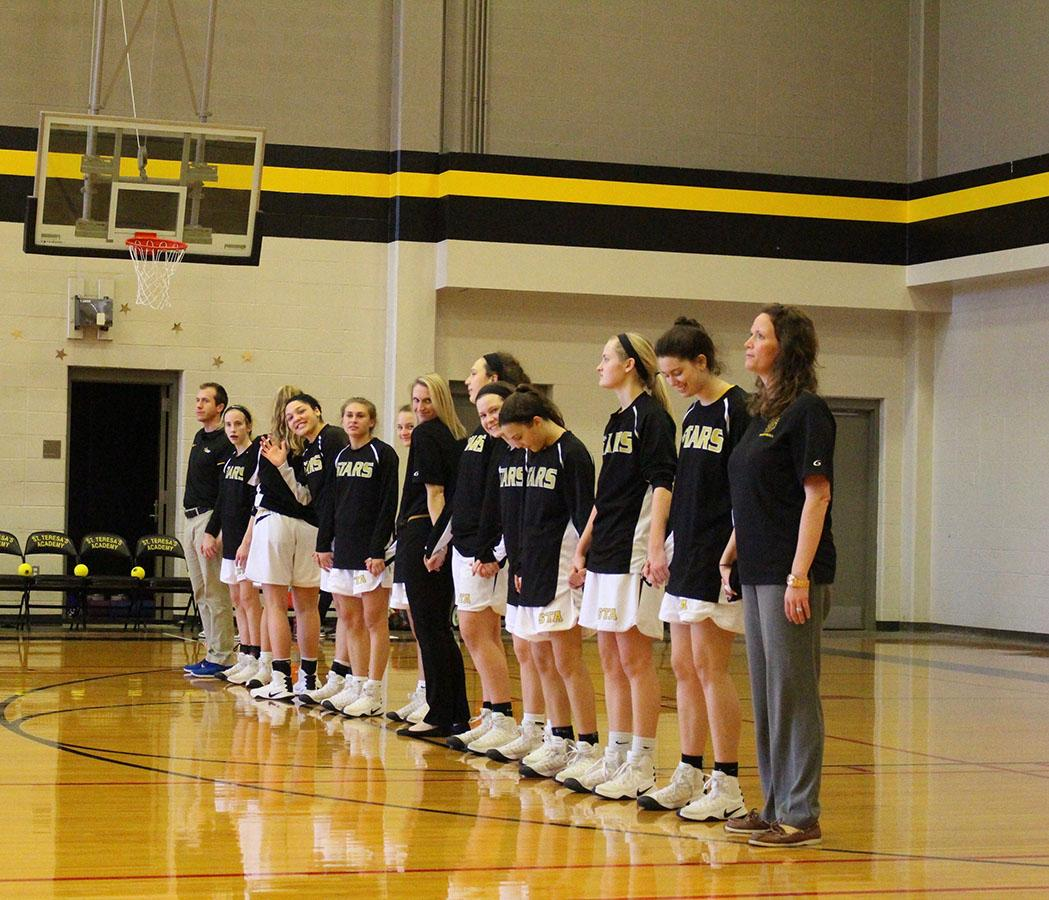 The Varisity basketball team stands in line for The National Anthem. photo courtesy of Olivia Woodbury