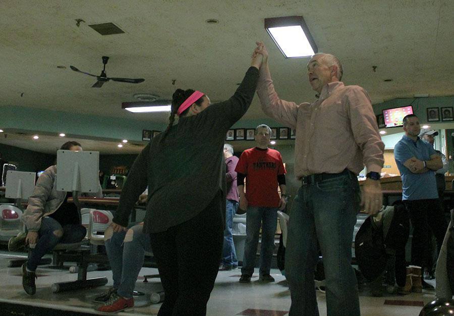 Junior Sloane Smith and her father Gary Smith high-five at Ward Parkway Lanes Jan. 8. photo by Meghan Baker