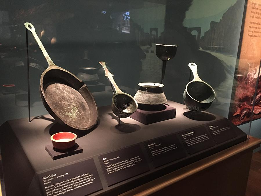 Kitchen utensils from Pompeii in Ancient Rome sit on display at Pompeii: The Exhibition at Union Station in Kansas City. photo by Lily Manning