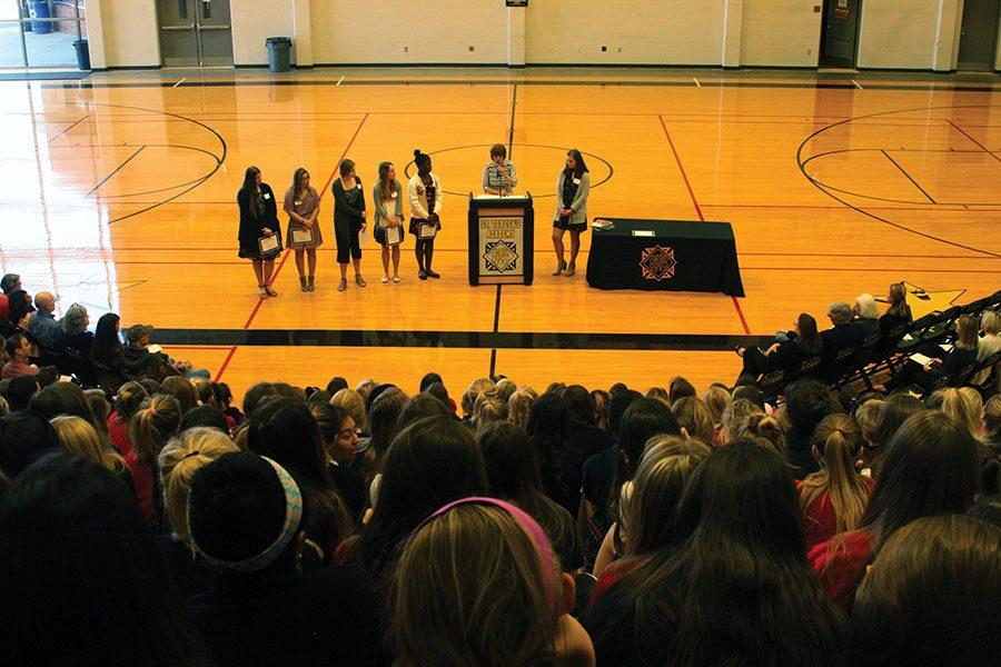 STA president Nan Bone introduces award finalists at the Mother Evelyn O'Neill award ceremony March 7. Finalists, from left, senior Eilis Leptien, junior Gabrielle Pesek, senior Lizy Hagan, junior Emma Boxx, freshman Faith Andrews-O'Neil and junior Claire Witt. photo by Cassie Hayes
