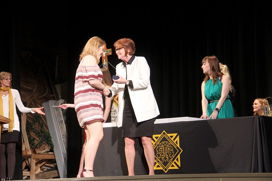President Nan Bone shakes junior Kate Jones'  hand as she hands Jones her class ring at the junior class ring ceremony Apr. 5. Jones was one of the first to receive her class rings because she is a junior class officer. photo by Sophie Sakoulas