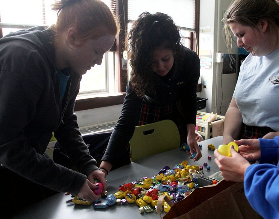 Seniors Isabel Burnett, from left, Haylee Gant and Serena Jonas help each other collect the candy they found in the Montag advisory community day Easter egg hunt April 12. photo by Sophie Sakoulas