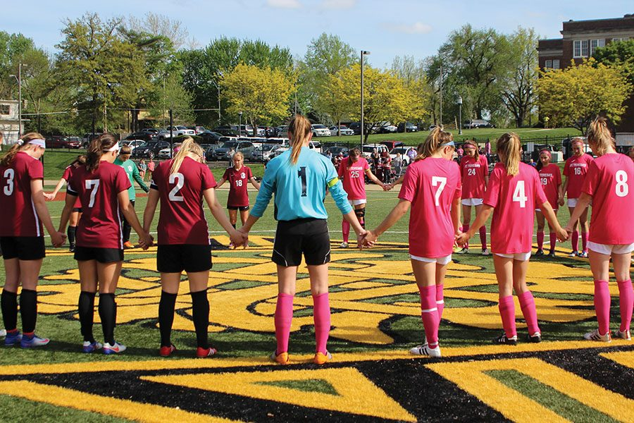 Soccer players from Lee's Summit North, in red, hold hands with players from St. Teresa's as they prayed before the game began. Both teams prayed for those affected by cancer at the annual-pink out soccer game April 18. photo by Anna Louise Sih