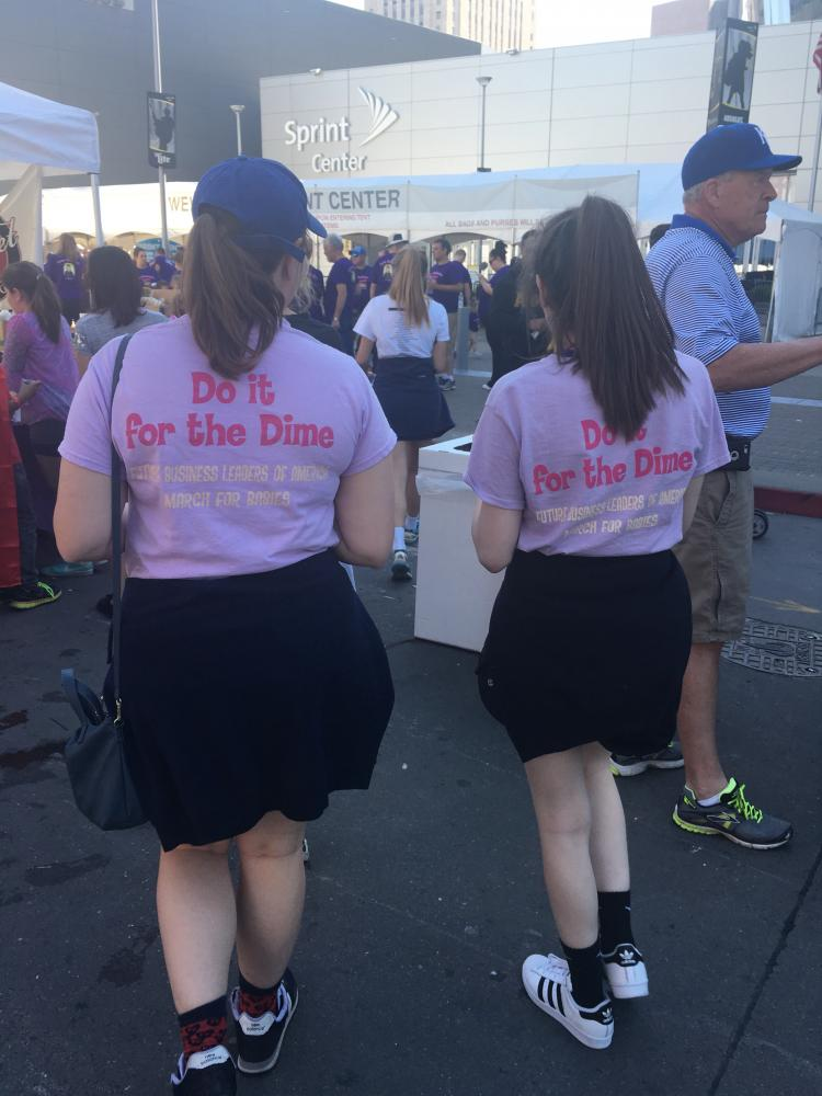 Juniors Maureen Egan and Taylor Staves walk along the route of the march sporting FBLA March of Dimes T-shirts. Photo by Gabby Mesa.