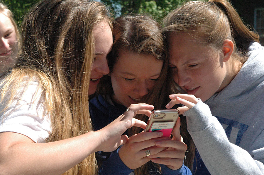 Seniors, from left, Molly Bird, Lizzy Williams, and Alexis Batliner look at a photo they just took together. photo by Riley McNett