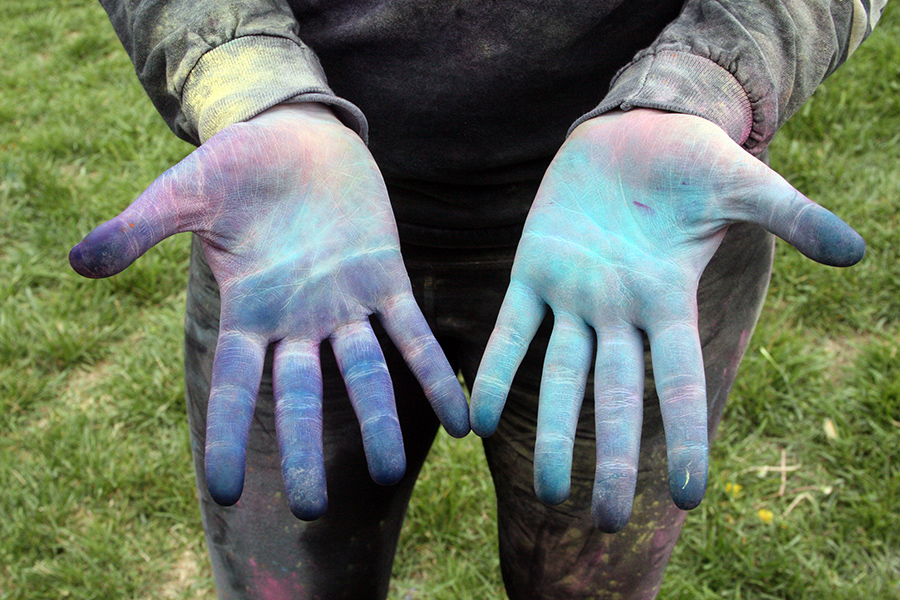 Senior Lilly McGonigle displays her hands, covered in colored corn starch, at the annual STA Color Throw April 21. Students are given a packet of ten raffle tickets to sell in order to participate. photo by Cassie Hayes