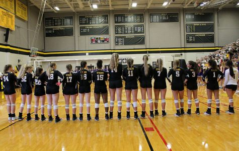 STA's varsity volleyball team lines up for the Pledge of Allegiance and National Anthem at St. Teresa's Academy Sep. 13. St. Teresa's beat Sion after three sets. photo by Meghan Baker