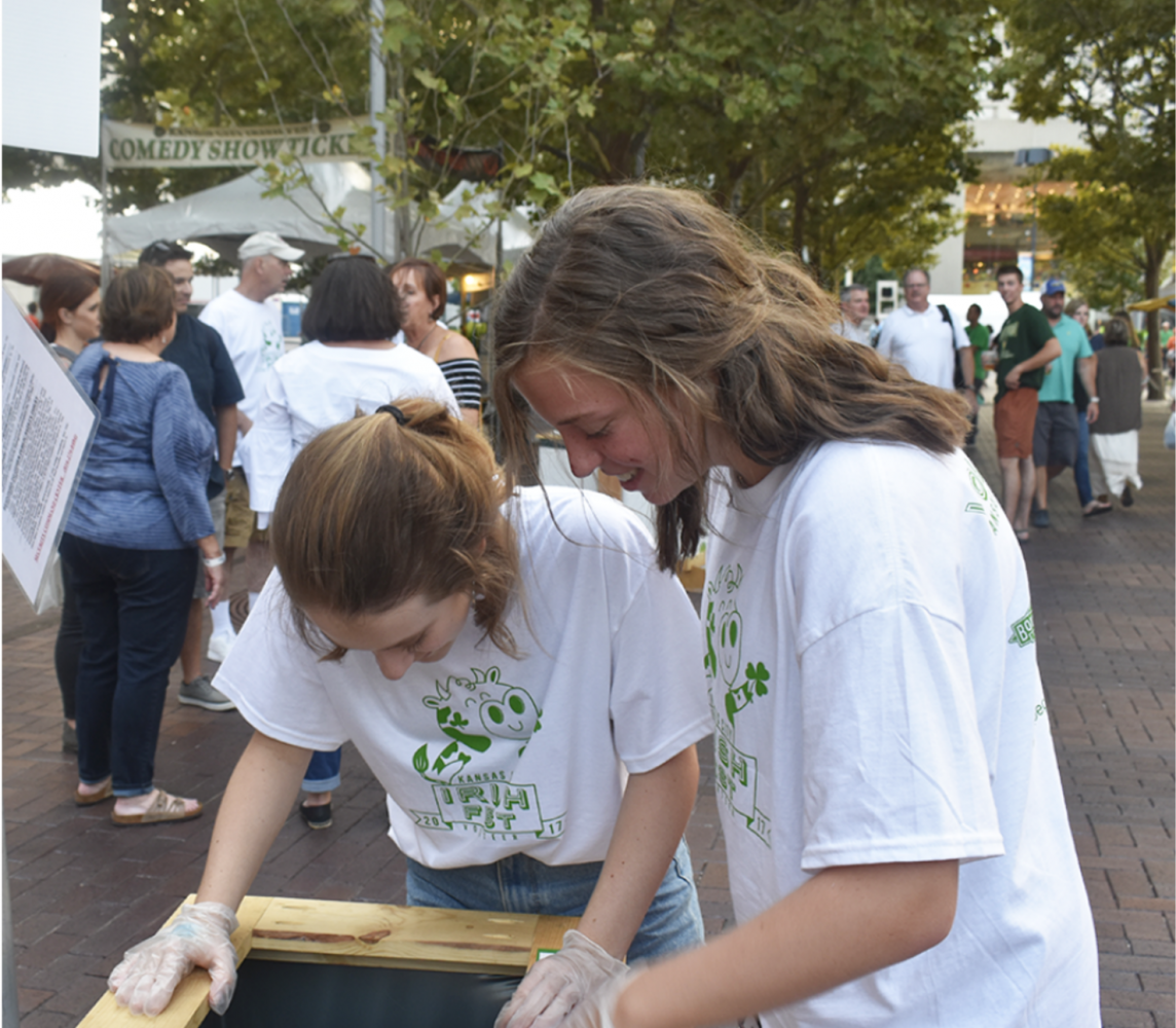 Junior volunteers Leah Dorris, left, and Madeline Loehr check the recycling bins for non-recyclable products Sept. 1. This was both girls first time volunteering at the Irish Fest. photo by Grace Fiorella