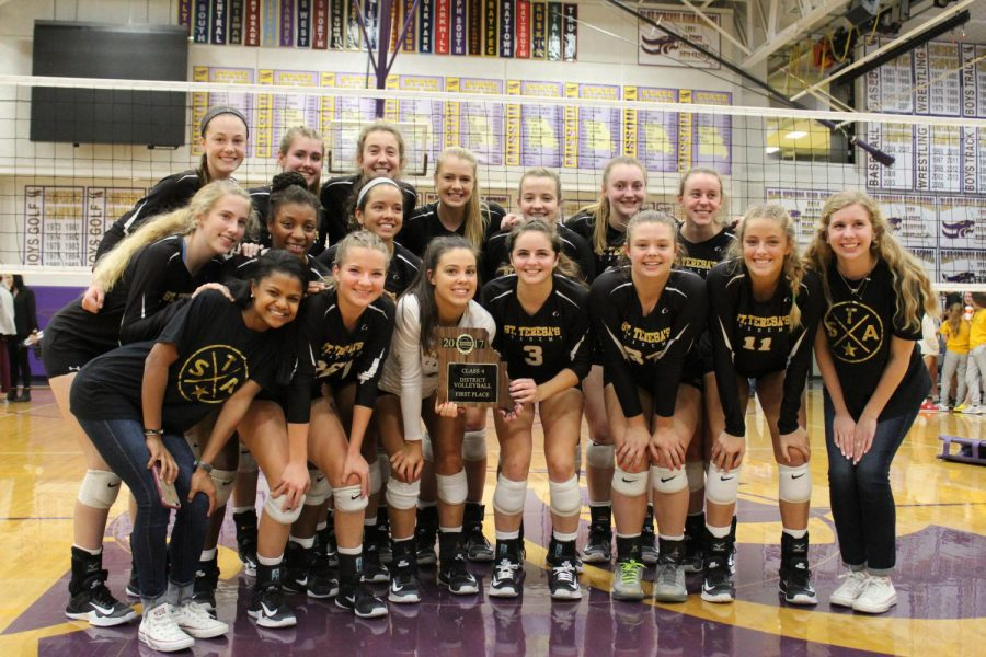 The+varsity+volleyball+team+stands+together+with+their+first+place+plaque+after+winning+Districts.