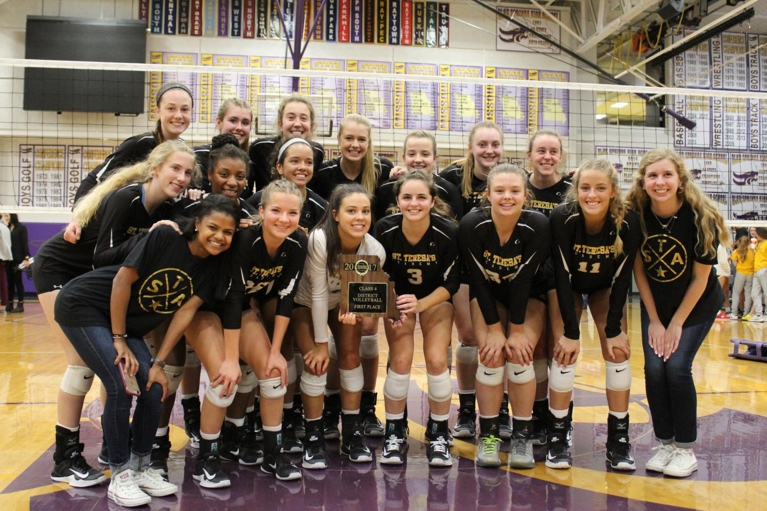 The varsity volleyball team stands together with their first place plaque after winning Districts.