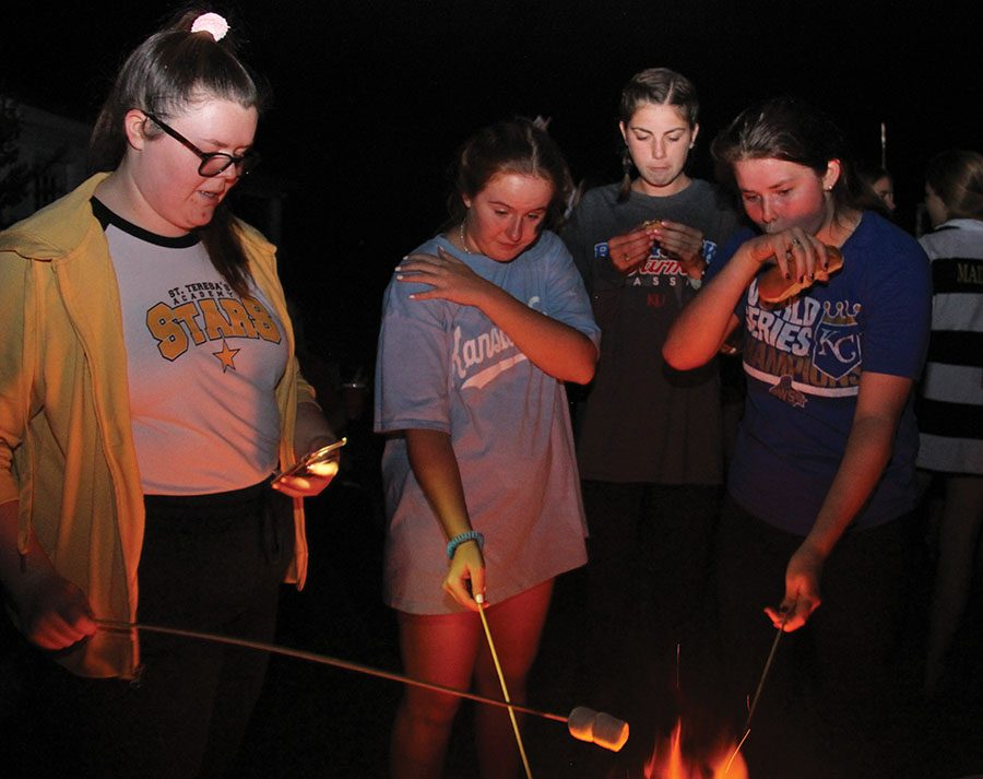 Seniors Sophia Brown, from left, Sally Dugan, Natalie Kistler and Claire Molloy gather around a bonfire to roast hot dogs and marshmallows together. The girls were at the camp out held Sept. 30 for the senior class of 2018. photo by Anna Louise Sih