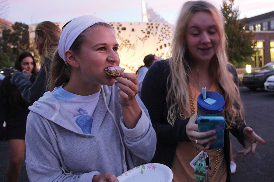 Senior Morgan Richards eats a pastry while talking to her friends Oct. 20 during the senior tailgate. The tailgate was held in the senior parking lot. photo by Anna Louise Sih