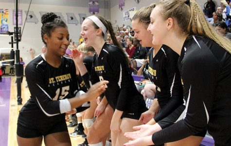Sophomore Torri Henry, left, high-fives her fellow teammates after coming off the court and onto the sidelines. photo by Anna Louise Sih