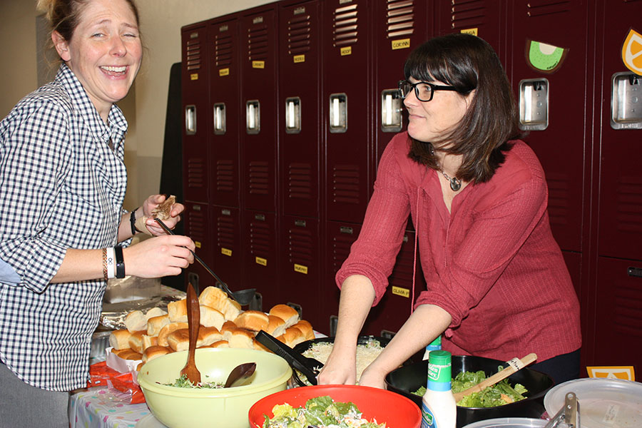 Math and computer science teachers Kim Sirridge and Vickie Albritton prepare food for the Donnelly second floor Thanksgiving party. The teachers tossed salad for the second floor advisories. photo by Trang Nguyen