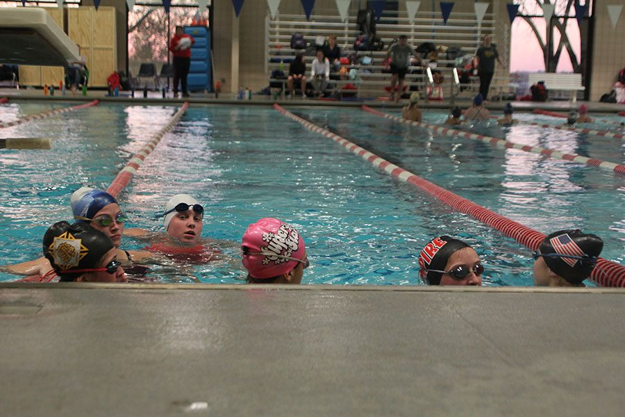 Swimmers rest at the end of the pool after swimming laps during tryouts Nov. 9. Swim team tryouts were held at Longview Community College. photo by Ella Kugler