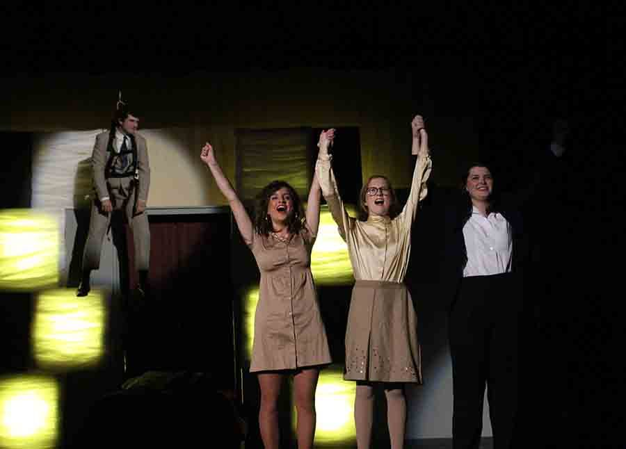 """Rockhurst High School junior Joe Hutchison, left, hangs from ropes while senior Bella Pichardo, junior Margaret Jordahl and senior Courtney Talken hold hands and sing """"Shine Like the Sun"""" during the act 1 finale of """"9 to 5."""" Hutchison played Franklin Hart, Jr., Pichardo played Doralee Rhodes, Jordahl played Judy Bernly and Talken played Violet Newstead in STA's production of """"9 to 5"""" Nov. 8 and Nov. 10. . photo by Madeline Loehr"""