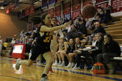 Sophomore Demi Spini reaches for the ball before it goes out of bounds Jan. 16.  STA lost to Bishop Miege, with a final score of 49-72. photo by Madeline Loehr