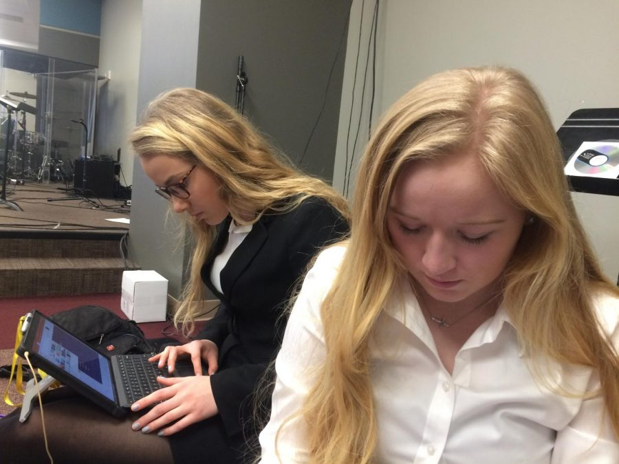 Sophomores Anne Chapman, left, and Anna Swanson prepare for their presentations at FBLA districts Feb. 2. photo by Mary Massman