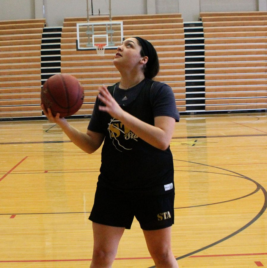 Senior Hailey Coleman looks up before she shoots a layup before practice Jan. 30. Coleman begins each practice with a shoot around followed by stretches. photo by Meghan Baker