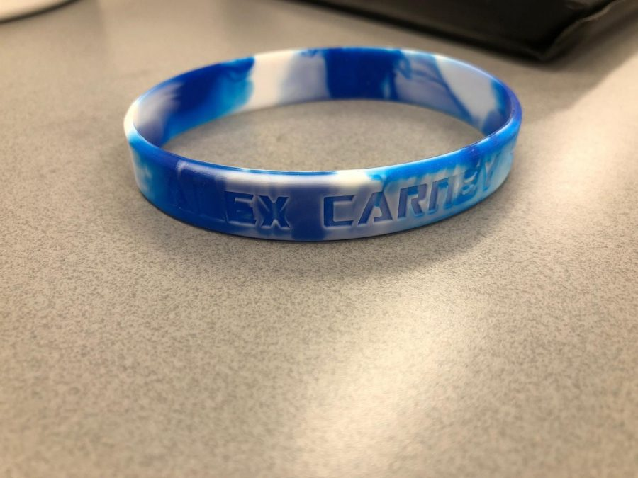 Sophomore Mia Falcon sold bracelets in memory of Alex Carney. Her bracelet sits on a table. photo courtesy of Mia Falcon