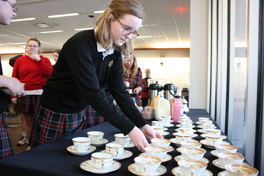 Senior Maura Graham grabs a teacup from the table at the CSJ tea party March 1 in WIndmoor. CSJ club moderator Jennifer Greene helped prep for the event. photo by Trang Nguyen