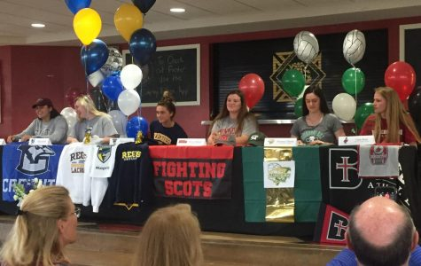 Seniors sit at their perspective tables decorated with apparel and banners of their college April 12. The seniors signed their intent letters to play in collegiate sports the following school year. photo by Anna Ronan