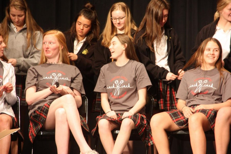 Sophomores Grace Decker, from left, Julia Flores, freshmen Zoey Ford, Lucy Sturr, Marie Bruck and Elise Johnson talk on stage in the auditorium as they get their hair cut and cut hair during the Inch-by-Inch event April 19. The hair and any other proceeds or donations went to Pantene Beautiful Lengths. photo by Trang Nguyen